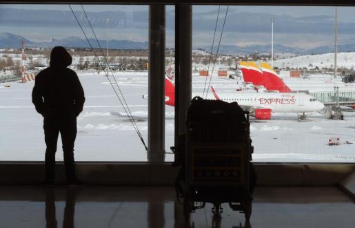 """MADRID, 10/01/2021.- El Aeropuerto Madrid Barajas-Adolfo Suárez mantiene suspendidas las operaciones al menos hasta este domingo por la tarde, """"cuando podrían retomarse de forma gradual"""", según ha informado este sábado el gestor aeroportuario Aena. En la imagen, una persona observa los aviones en la T-4. EFE/Kiko Huesca El aeropuerto de Barajas estará cerrado al menos hasta esta tarde"""