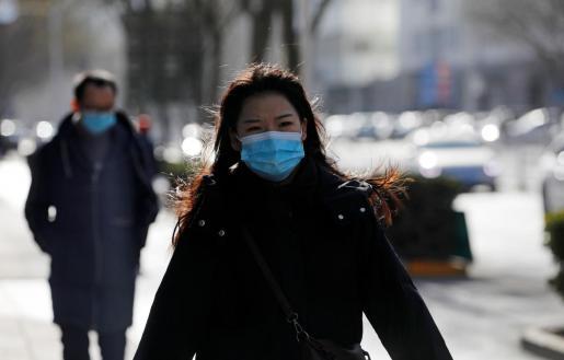 Un mujer, con mascarilla, pasea por una calle en Beijing.