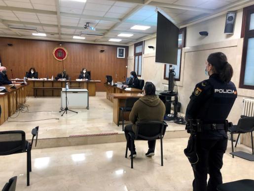 El acusado, custodiado por una agente de la Policía Nacional, en el juicio celebrado este lunes en la Sección Primera de la Audiencia de Palma.