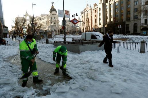 Unos operarios retiran nieve de la acera este lunes en la calle Alcalá de Madrid.