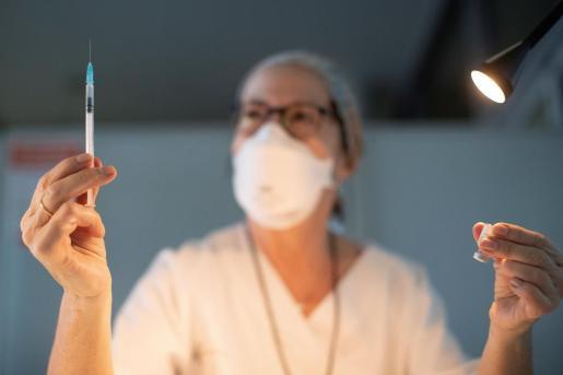 Una enfermera preparando las vacunas .