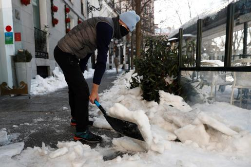 Un hombre retira nieve de la acera en Madrid.