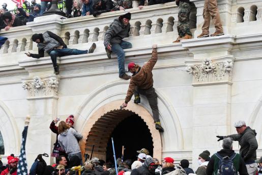 Los partidarios del presidente de los Estados Unidos, Donald Trump, treparon a los muros del Capitolio de los Estados Unidos durante una protesta contra la certificación de los resultados de las elecciones presidenciales de los Estados Unidos de 2020 por parte del Congreso de los Estados Unidos.