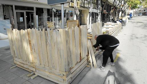 El propietario de un local en la avenida Argentina de Palma retira, el jueves, su terraza entarimada.