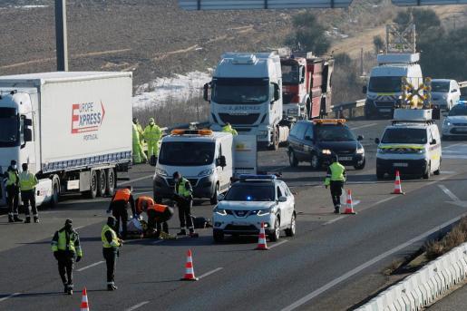 Agentes de la Guardia Civil junto al cuerpo sin vida de uno de los conductores de tres camiones que han fallecido en la A-6, en Tordesillas (Valladolid), tras ser atropellados por un cuarto camión, cuando intentaban apagar el incendio que se había producido en uno de los articulados.
