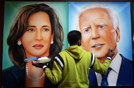 El artista indio Jagjot Singh Rubal da los toques finales a las pinturas que muestran al presidente electo de Estados Unidos, Joe Biden (derecha) y a la vicepresidenta electa Kamala Harris (izquierda) en la víspera de su ceremonia de juramento, en el taller de su casa en Amritsar.