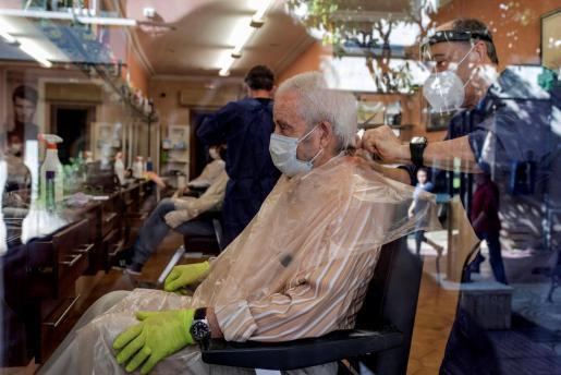 Imagen de una peluquería con mascarillas y mamparas.
