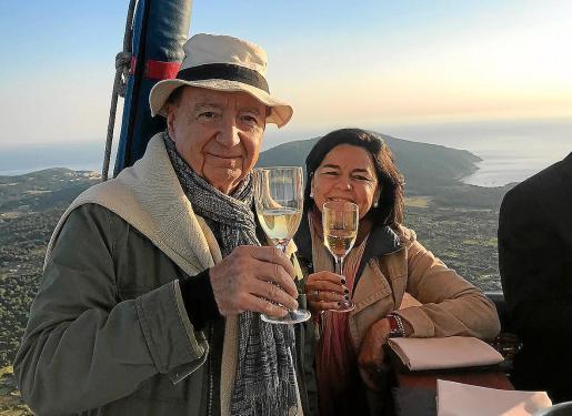 José Carlos Capel, junto a Julia Pérez, de Gastroactitud, durante un desayuno en globo preparado por Andreu Genestra, con la costa de Capdepera al fondo.