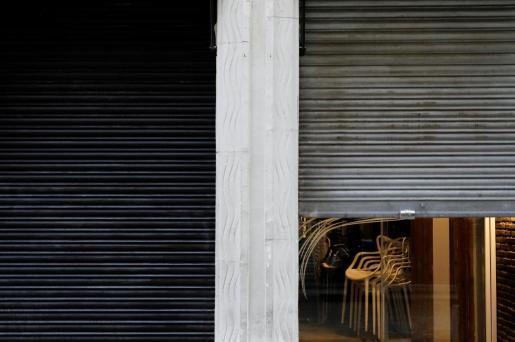 Sillas recogidas en un restaurante de Valencia que cierra la persiana.