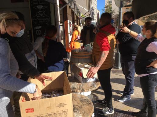 Ambas organizaciones han repartido más de 400 bocadillos y comida para los necesitados en el Mercado del Olivar.