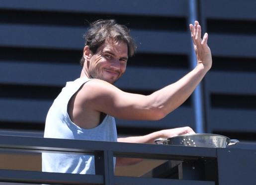 Rafael Nadal saluda a un grupo de aficionados desde la habitación de su hotel en Adelaida.