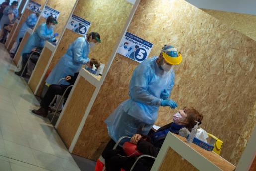 Varios trabajadores sanitarios realizan una prueba PCR durante un cribado poblacional en Ourense.