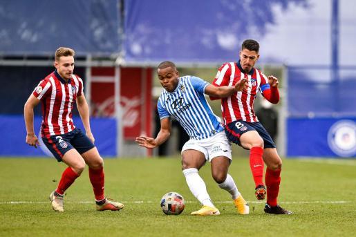 El delantero del Atlético Baleares Vinicius Tanque controla un balón ante la presión del jugador del Atlético de Madrid B Toni Moyá en un momento del partido disputado este domingo entre ambos equipos en el Cerro del Espino.