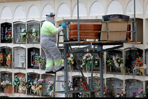 Un operario del cementerio de Santa Margarida de Montbui (Barcelona) se dispone a introducir un féretro en un nicho.