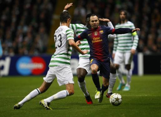 Andres Iniesta disputa un balón a los jugadores del Celtic Victor Wanyama y Mikael Lustig .