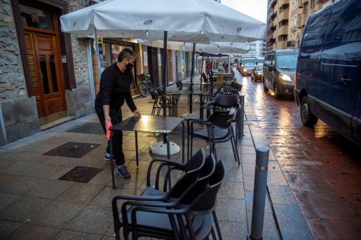 Un camarero de una tabernera de Vitoria monta la terraza de su bar.