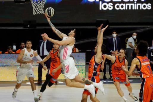 El jugador argentino del Real Madrid Gabriel Deck (c) entra a canasta ante los jugadores del Valencia Basket.