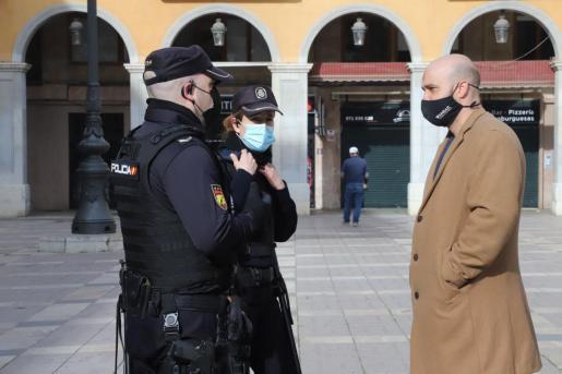 Víctor Sánchez, junto a dos policías, en la plaza Major de Palma.