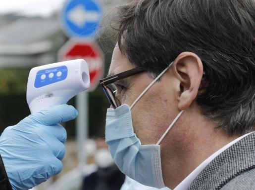 El candidato del PSC a la presidencia de la Generalitat, Salvador Illa, se somete a un control de temperatura, momentos antes de ejercer su derecho a voto en el Centro Cultural La Roca del Vallés este domingo durante las elecciones autonómicas.