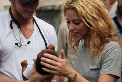 La cantante colombiana Shakira, embajadora de buena voluntad de Unicef, observa a un niño junto a un médico, durante su visita al campo de desplazados ubicado en el Club de Campo de Petion Ville, Puerto Príncipe (Haití).