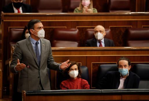 El presidente del Gobierno, Pedro Sánchez (izq), en presencia de los vicepresidentes Carmen Calvo y Pablo Iglesias, interviene durante una nueva sesión de control.