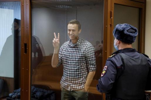El líder opositor ruso Alexéi Navalni hace el signo de la victoria desde una celda de cristal durante una nueva sesión de su batalla en los tribunales.