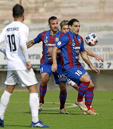 Rubén Jurado, delantero del Poblense, controla el balón en presencia de Aitor Pons.