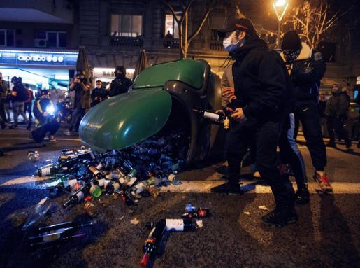 Manifestantes se disponen a lanzar botellas a la policía durante la protesta contra la detención y prisión del músico y rapero Pablo Hasél.