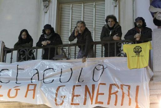 Una veintena de actores, encabezados por el actor Willy Toledo (c), desplegando una pancarta desde la fachada del Teatro Español.