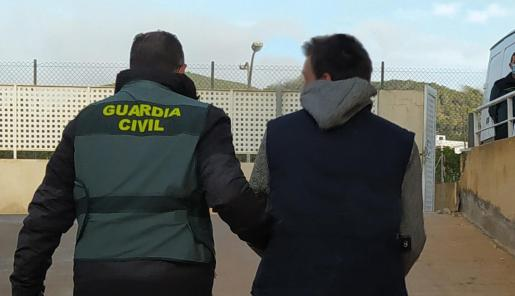 Un agente de la Guardia Civil con uno de los presuntos implicados en los robos.