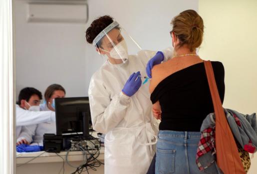 Personal sanitario vacuna a una mujer en el recinto del antiguo hospital Son Dureta.