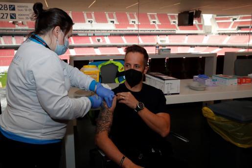 Un profesional recibe la primera dosis durante el primer día de vacunación contra la covid-19 en el Wanda Metropolitano, el estadio del Atlético de Madrid.