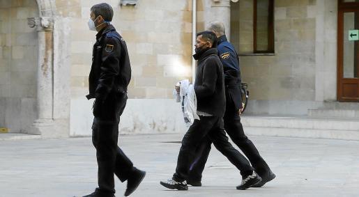 El acusado, custodiado por dos policías, en el patio de la Audiencia Provincial.