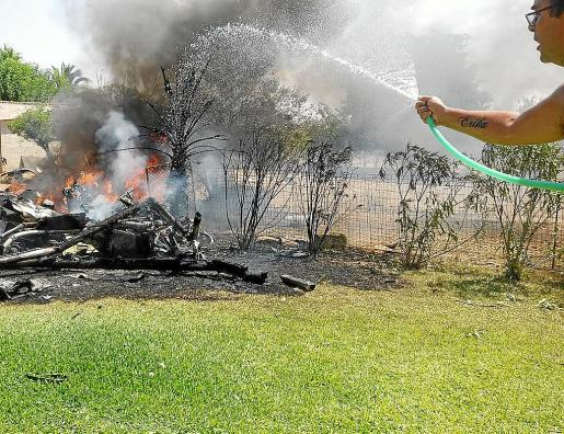 Un vecino trata de apagar con una manguera el fuego declarado en una de las aeronaves siniestradas en Inca.