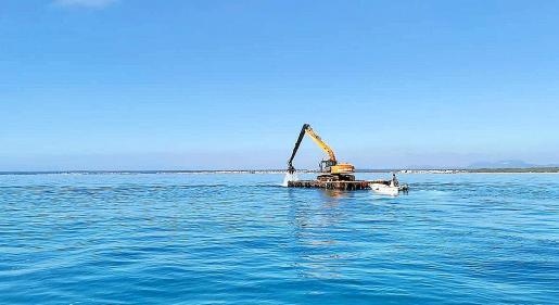 Imagen de la excavadora sobre el mar con sa Ràpita y ses Covetes de fondo.