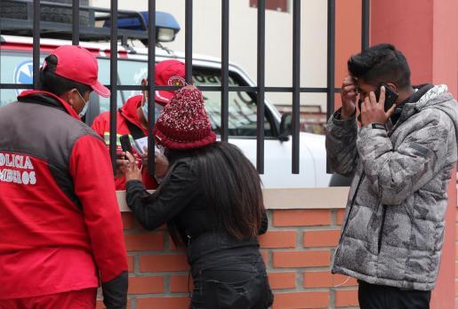 Un bombero habla con una mujer que espera información tras el accidente en el que murieron varios estudiantes.