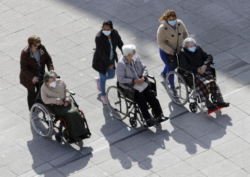Tres mujeres dependientes pasean este miércoles en Bilbao. Las residencias de ancianos de los tres territorios vascos permitirán a sus usuarios realizar un mínimo de cuatro salidas y recibir dos visitas de dos familiares a la semana.