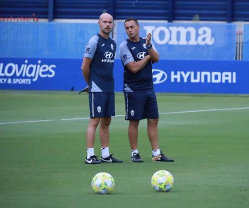 El nuevo entrenador del Atlético Baleares, Xavi Calm -izquierda-, atiende las explicaciones del recientemente destituido Jordi Roger durante un entrenamientos del equipo en el Estadi Balear.