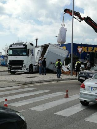 Imagen del camión siniestrado, con parte de la carga sobre la vía y la acera.