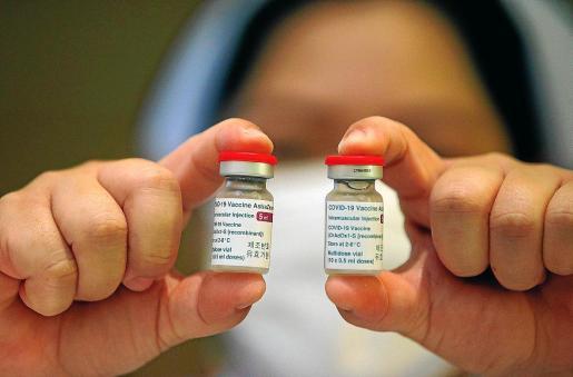 Una enfermera muestra dos viales de la vacuna contra la COVID-19 desarrollada por AstraZeneca.