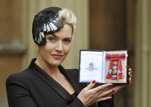 La actriz británica Kate Winslet enseña su título de Comandante del Imperio Británico.