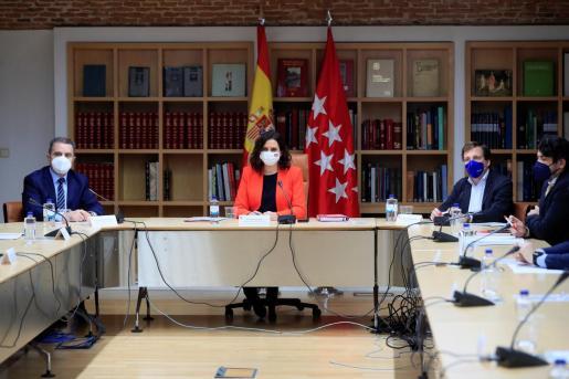La presidenta de la Comunidad de Madrid, Isabel Díaz Ayuso (c), preside la reunión del Plan Territorial de Protección Civil de la Comunidad de Madrid junto al alcalde de la capital, José Luis Martínez-Almeida (d), y el delegado del Gobierno en la Comunidad de Madrid, José Manuel Franco (i), este lunes, para hacer el seguimiento de la pandemia.