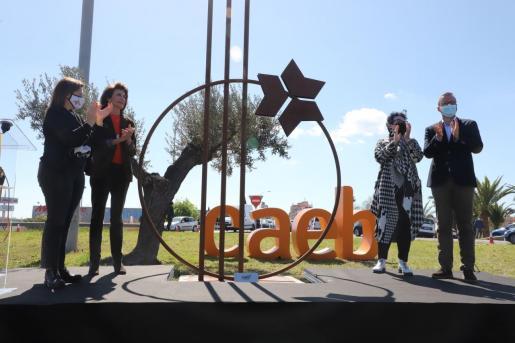 Autoridades y empresarios posan ante la escultura de María Genovart inaugurada este miércoles.