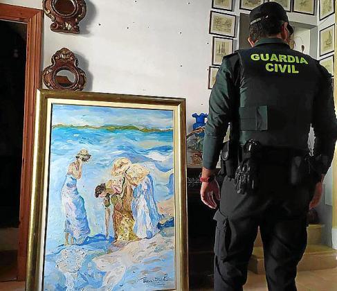 En la imagen, un guardia civil observa el cuadro recuperado en el robo de Montuïri, que según la propietaria está valorado en 4.000 euros.