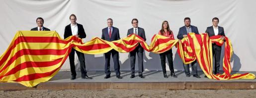 Los candidatos a la presidencia de la Generalitat (de izq. a dcha.) Alfons López Tena (SI), Joan Herrera (ICV), Pere Navarro (PSC), Artur Mas (CiU), Alicia Sánchez Camacho (PPC), Oriol Junqueras (ERC) y Albert Rivera (C's), posan con una 'senyera' como nexo de unión entre todos los partidos, durante la jornada de reflexión de la elecciones catalanas.