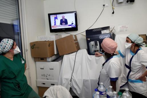 personal sanitario viendo la intervención del primer ministro Jean Castex.
