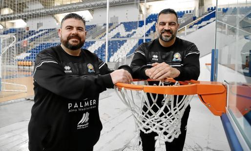 Pau Tomàs y Álex Pérez, entrenadores del Palmer Alma Mediterránea Palma, posan en una de las canastas del Palau d'Esports de Son Moix durante la entrevista.