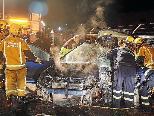 Los bomberos atienden al conductor que provocó el accidente.