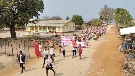 Los manifestantes sostienen una foto de Aung San Suu Kyi y ondean la bandera de la Liga Nacional para la Democracia (LND) durante una marcha en el distrito de Dawei.
