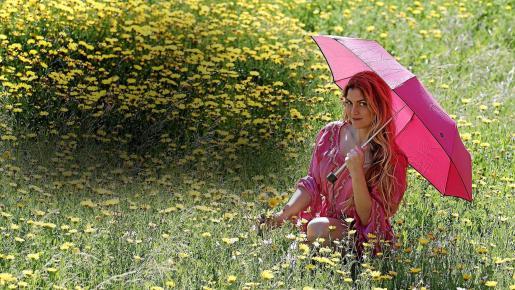 Las flores silvestres llenan el campo mallorquín en el inicio de la primavera. Laville posa con un complemento esencial para días de lluvia: el paraguas.